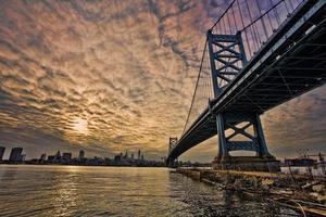 een gestileerde afbeelding van een brug die naar een stad leidt foto