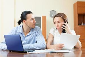 koppel mobiel bellen over financiële documenten foto