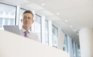 portret van zakenman met laptop en documenten op reling foto