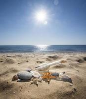 fles op een zand foto
