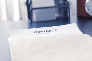 contract in een bruine envelop op zwarte tafel foto