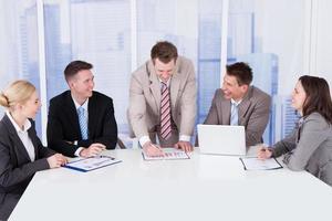 mensen uit het bedrijfsleven bespreken grafiek aan vergadertafel foto