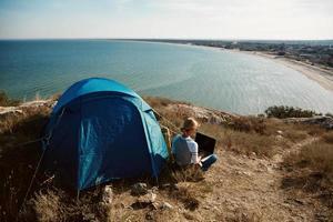 gelukkige vrouw zitten in de buurt van tent met laptop, uitzicht op bergen foto