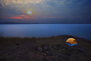 camping tent naast zee strand met ochtendhemel foto
