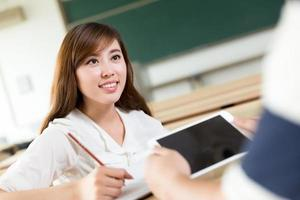 twee Aziatische student bespreken inhoud op tablet