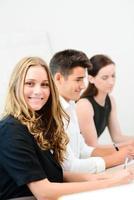 vrolijke jonge zakenvrouw met partners in een vergaderruimte foto