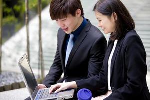 jonge vrouwelijke en mannelijke Aziatische directeur die laptop met behulp van
