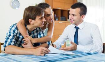 zelfverzekerde verkoper en jonge echtgenoten die contract bespreken foto