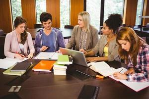 lachende studenten werken samen aan een opdracht