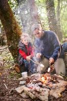 vader en zoon roosteren marshmallows op een kampvuur