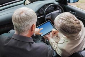 volwassen partners werken samen aan tablet in stijlvolle auto foto