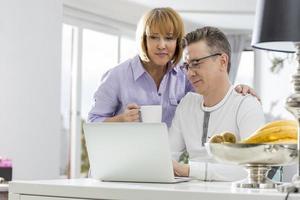 volwassen paar met behulp van laptop samen aan tafel in huis foto