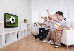 jubelende familie die televisie kijkt foto