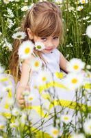 schattig kind meisje op kamille veld
