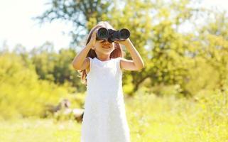 klein meisje kind kijkt in de verrekijker zomer foto