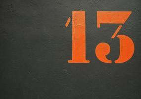 een oranje stenciled nummer 13 op een zwarte achtergrond