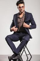 elegante jongeman zijn jas zittend op een stoel openen foto