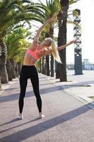 vrouwelijke atleet met perfecte figuur doen strekt zich uit buiten te oefenen