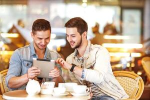 twee jonge mannen / studenten met behulp van tablet-computer in café