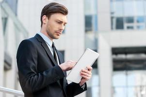 succesvolle zakenman. vrolijke jonge mannen in formalwear met digitale tablet foto
