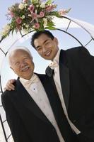 bruidegom met vader onder archway