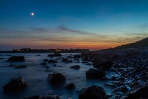 rotsachtige strandzonsondergang foto