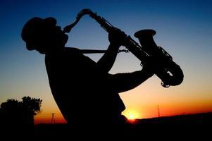 saxofonist bij zonsondergang foto
