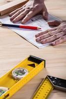 mens handen op blauwdruk met tools foto