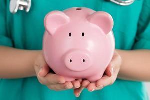vrouwelijke arts met spaarvarken
