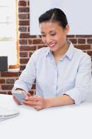 vrouwelijke uitvoerende tekstberichten in bureau foto