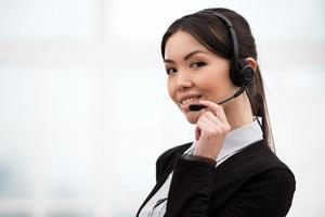 Aziatische callcenter vrouwelijke exploitant die hoofdtelefoons met behulp van foto