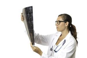 jonge vrouwelijke arts die een röntgenstraal bekijkt foto
