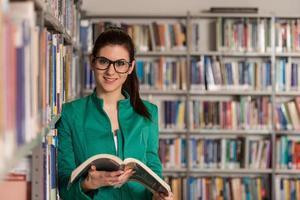 gelukkig vrouwelijke student met boek in bibliotheek foto