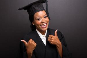 Afrikaanse vrouwelijke universitair afgestudeerde duimen omhoog foto