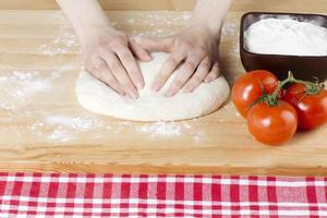 vrouwelijke hand kneden van deeg voor pizza