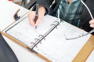 zakenvrouw merkt een afspraak in haar dagboek foto