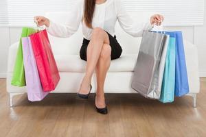 vrouw met veelkleurige boodschappentassen thuis foto