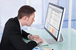 geconcentreerde zakenman die op computer in bureau werkt foto