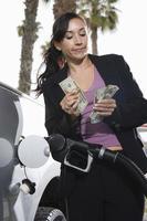 jonge vrouw geld tellen bij tankstation foto