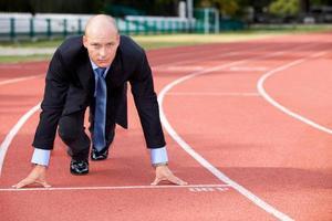 zakenman aan de startlijn van de atletiekbaan foto