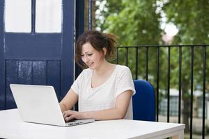 gelukkige jonge onderneemster die aan laptop bij bureau werkt foto
