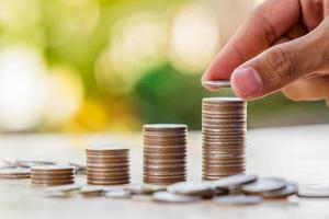 hand zetten geld munten stapel groeiende zaken, geld besparen con foto