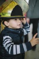 kleine jongen in de helm van een brandweerman foto