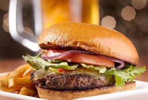cheeseburger met mok bier op achtergrond foto
