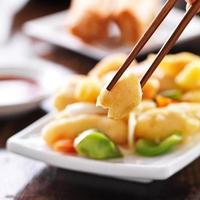 het eten van Chinese zoetzure kip met stokjes foto