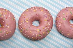 roze donut op blauw gestreepte achtergrond foto