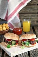 huisgemaakte hamburgers met tomaten, uien en augurken foto