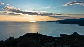 zonsondergang op de baai van toroni met schildpad eiland in de achtergrond, sithonia foto