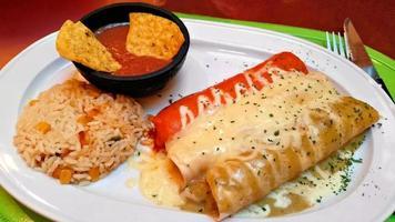 rood witte en groene enchiladas met rijst en bonen foto