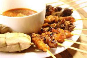 plaat van saté eten op een houten tafel